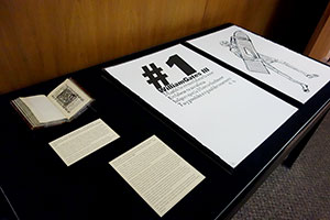 Overview of materials on display, showing a cradled book and two pages from a very large set of prints.