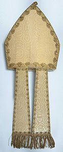 Studio photograph of the bishop's miter, a pointed cream-colored headpiece with fabric strips that extend down from the bottom edge.